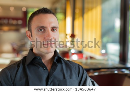 an handsome man sitting in a trendy restaurant and smiling - stock photo