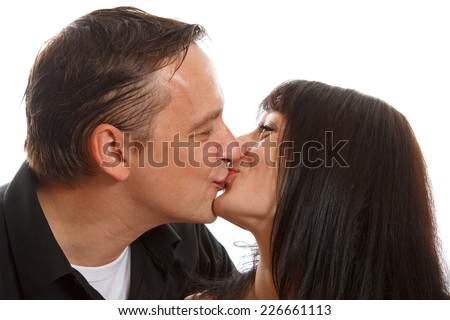 An happy couple kissing each other while smiling - stock photo