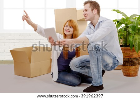 an happy couple planning decor in new home  - stock photo