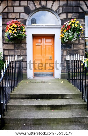 An historic European entrance way with bright orange door - stock photo