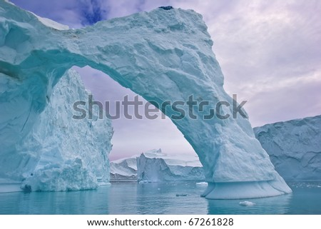 an ice arch carved by the wind in a giant iceberg, greenland - stock photo