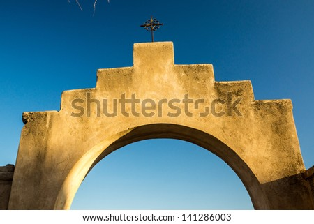 An iconic adobe archway and crucifix at a Spanish mission in Arizona - stock photo