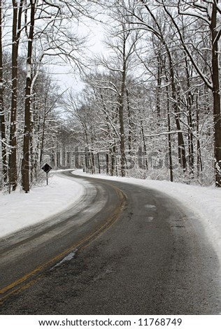 An icy and snowy road leading into the forest - stock photo
