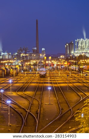 An illuminated railroad yard with trains and other industry in the background at night - stock photo