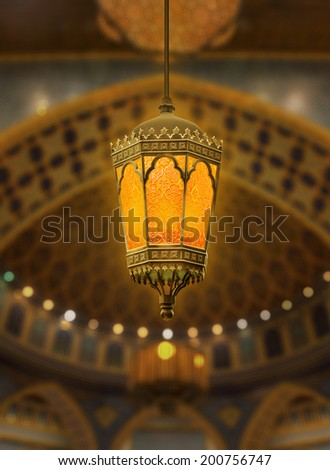 An illuminated Ramadan lantern against islamic architecture - stock photo