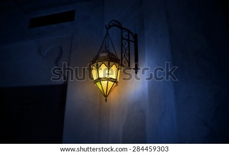 An illuminated wall mounted islamic lamp hanging on the wall. - stock photo