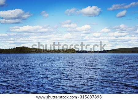 An image of a beautiful landscape from Finland. In this image a big lake is in front of the forest far away. Some clouds are in the sky. Image has a vintage effect applied. - stock photo