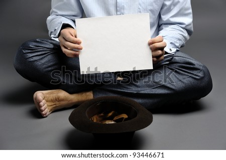 An image of a beggar with a hat and a sheet of paper - stock photo