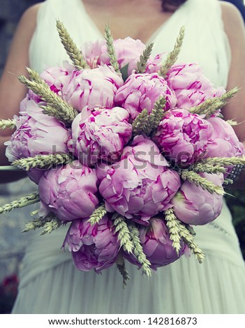 An image of a bride holding a peonies bouquet - stock photo
