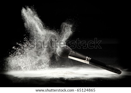 an image of a cosmetic powder brush, thrown in white loose powder, shot on black backgrownd. - stock photo