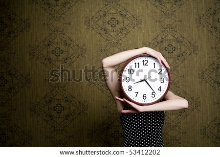 An image of a girl holding a big clock - stock photo