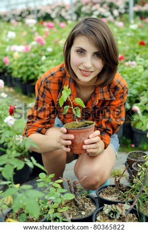An image of a girl with a plant in a pot - stock photo