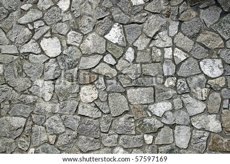 An image of a grungy weathered limestone rubble wall surface. - stock photo