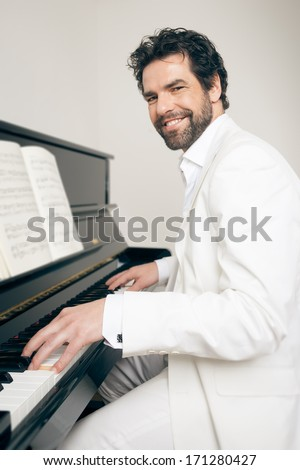 An image of a handsome man playing the piano - stock photo
