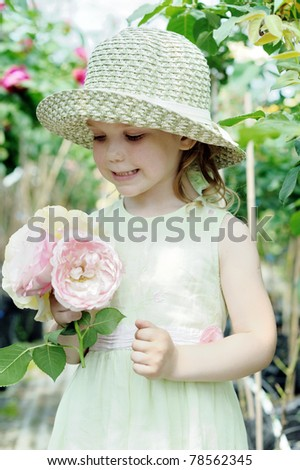 An image of a little girl with big roses - stock photo