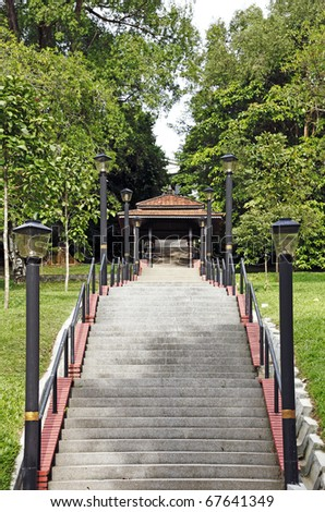 An image of a long concrete stairway to a rustic gateway into a green park. - stock photo