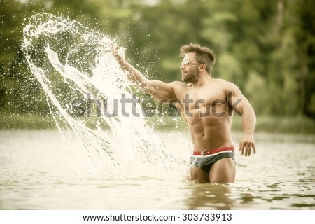 An image of a muscular man in the lake playing with the water - stock photo