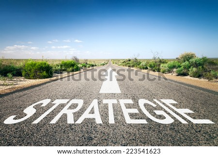An image of a road to the horizon with text strategy in german language - stock photo