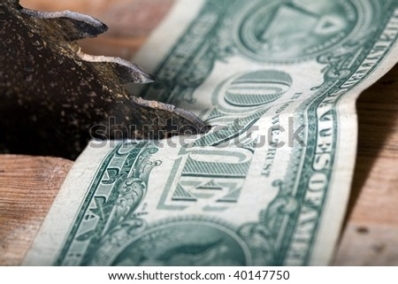 An image of a saw and one dollar - stock photo