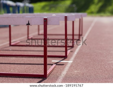 An image of a training hurdles in sunlight on a red surface. - stock photo
