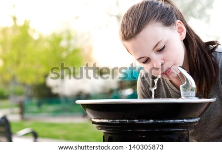 An image of a young girl drinking from a water fountain - stock photo