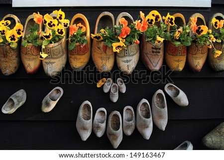 An image of clogs in a wall as flowerpots - stock photo