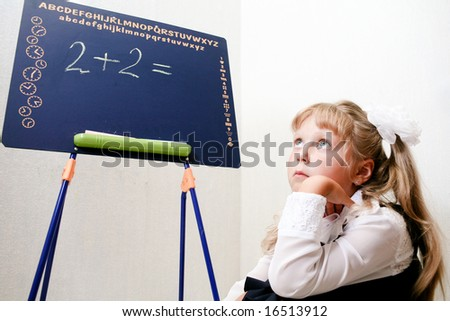 An image of Little girl sitting near chalkboard. - stock photo