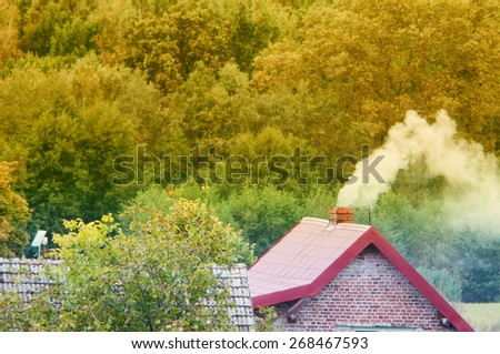 An image of moke coming out of chimney - stock photo