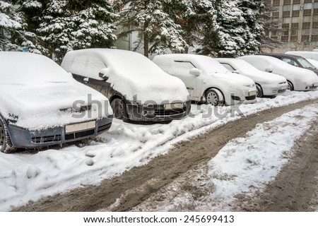 an image of snow covered cars in parking lot - stock photo