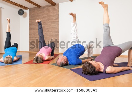 An image of some people doing yoga exercises - Eka Pada Setu Bandha Sarvangasana  - stock photo