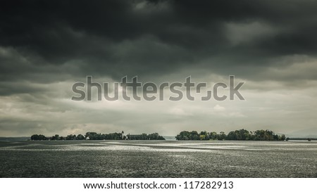 An image of the Chiemsee in Bavaria Germany with a dramatic sky - stock photo