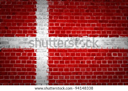 An image of the Denmark flag painted on a brick wall in an urban location - stock photo
