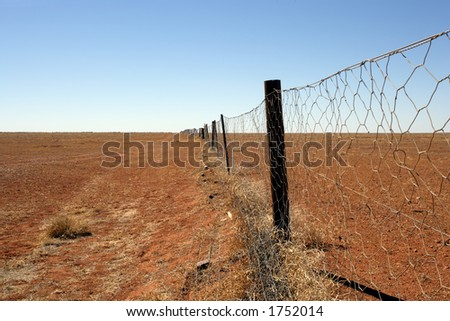 An image of the Dingoe fence in the Australian Outback.  The fence is 9600 kilometres long and spans the entire country, keeping the dingoes out of the south where the sheep graze. - stock photo