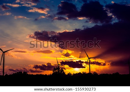An image of wind turbines at sunset - stock photo