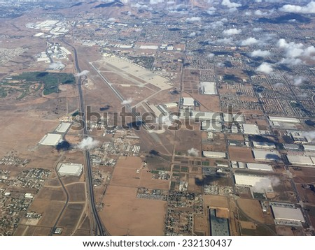 An image shot from an airplane shows an industrial expanse lined with residential tracts of homes.  - stock photo