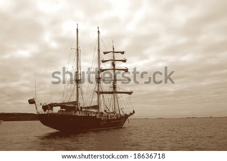 An image toned sepia to resemble a ghost ship of pirates alone in the ocean. - stock photo