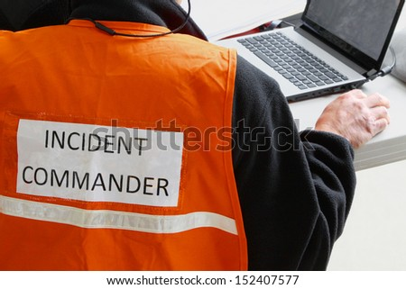 An Incident Commander is in charge at any natural or man made disaster or major accident. Telecommunications is very important to keep on top of the situations as they develop. - stock photo