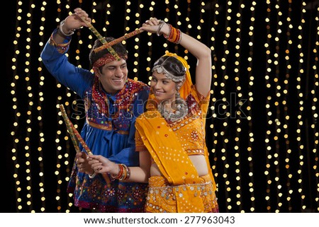 An Indian couple in traditional wear performing Dandiya Raas against neon lights - stock photo