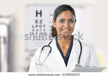 An Indian female nurse with an eye test chart in the background. - stock photo
