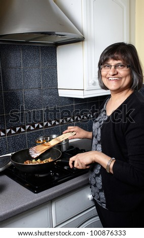 An indian lady in the kitchen making a curry - stock photo