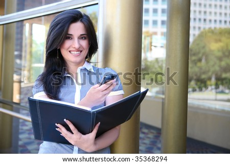 An Indian pretty business woman outside office on phone - stock photo