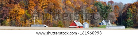An Indiana farm with red barn is backed by a hillside full of colorful fall foliage in this panoramic photograph. - stock photo
