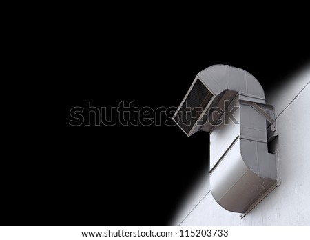An Industrial metal exhaust vent outlet attached to a wall, isolated against black. - stock photo