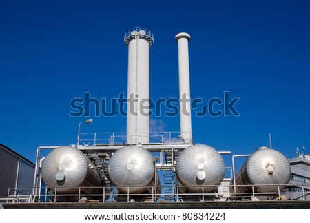 An industrial plant with silver tanks with smokestacks - stock photo