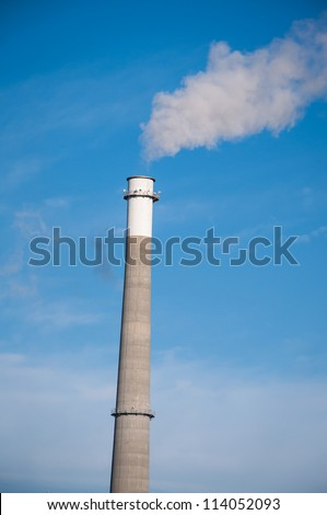 An Industrial Smoke Stack Releases Pollution into the Air - stock photo