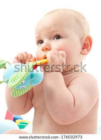 An infant holding a toy with both hands. - stock photo