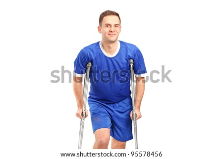 An injured soccer football player on crutches isolated against white background - stock photo