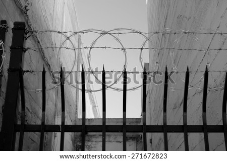 """An inner city fence with sharpened vertical bars, barbed wire and concertina wire conveys the message. """"Keep Out."""" (monochrome image) - stock photo"""