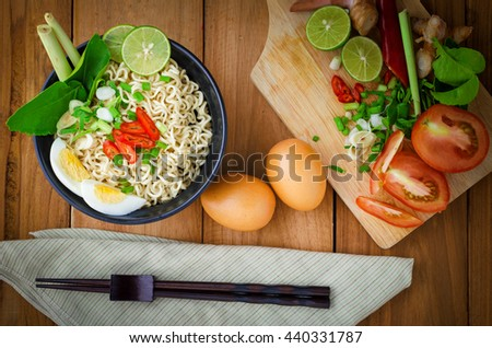An instant noodle in black bowl cooked spicy taste with some ingredients and chopstick and eggs put beside. - stock photo