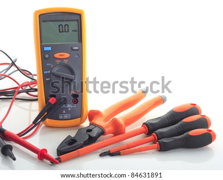 An insulation tester with 3 electrical screw driver and 1 plier. Isolated white background. Insulation tester reading 0.0 volt dc. - stock photo